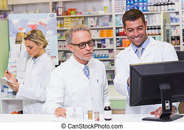 Team of pharmacists looking at computer at the hospital...