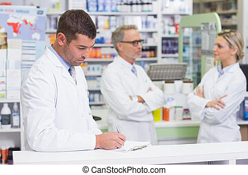 Pharmacist in lab coat writing a prescription in the...
