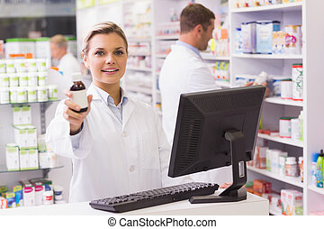 Pharmacist showing medicine bottle at hospital pharmacy