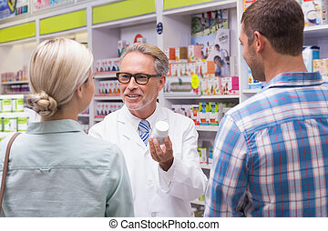Senior pharmacist explaining the pills to patient at...