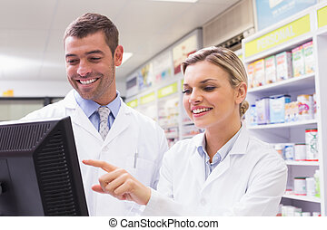 Pharmacists looking at computer - Team of pharmacists...