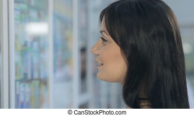 Young girl talking to pharmacist in drugstore - Young girl...