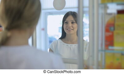 Pharmacist talking to a girl in a drugstore - Pharmacist...