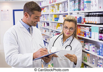 Pharmacist looking a medication for a prescription in the...