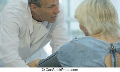 The doctor puts sleeve of tonometer to the patient and...