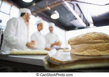 Fresh bread with bakers behind him in the kitchen of the...