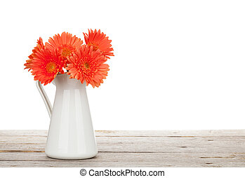 Orange gerbera flowers in pitcher on wooden table Isolated...