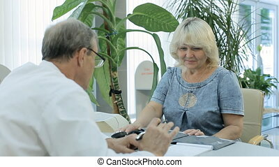 The doctor writes a prescription, puts sleeve of tonometer to patient and measures the pressure