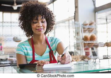 sonriente, camarera, escritura, en, bloc,