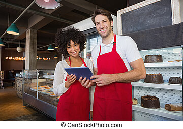 Happy co-workers in red apron holding tablet