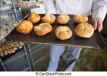 Mid section of chef showing tray of bread at the bakery