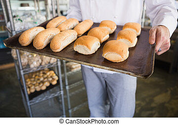 Mid section of a baker holding tray with bread at the bakery