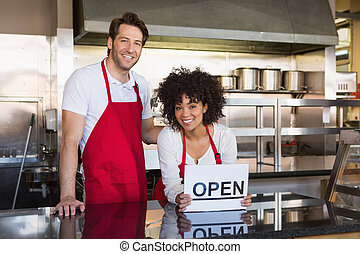 Smiling co-workers posing with open sign at the bakery