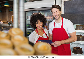 Smiling colleagues holding tablet pc at the bakery
