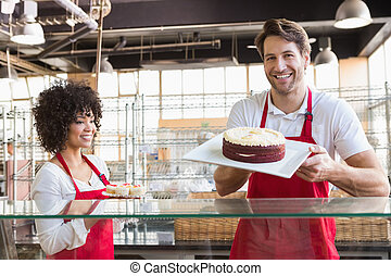 Smiling colleagues in uniform showing cakes at the bakery