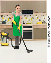 woman vacuuming kitchen floor - young woman vacuuming...