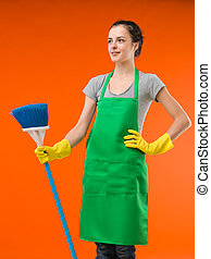 happy cleaning lady standing and holding broom, on orange...