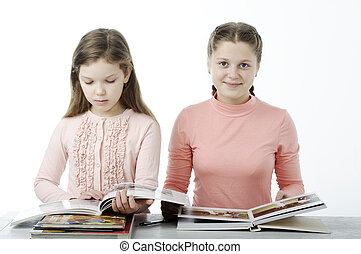 Little girls read books at the table on white