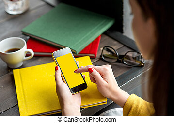 Using smart phone - Woman using smart phone on the table...