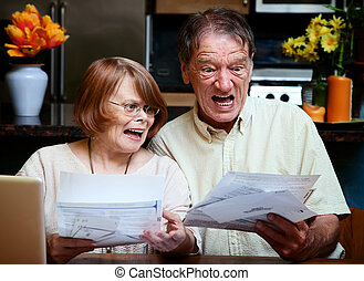 Senior couple at home with many bills - Senior couple at...