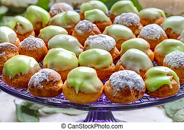 vivid profiteroles on glass tray - Delicious sweet buffet...