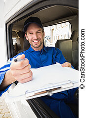 Happy delivery man showing clipboard to sign to customer...