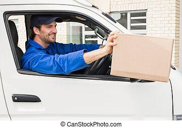 Delivery driver offering parcel from his van outside the...