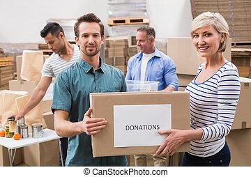 dois, voluntários, segurando, Um, doações, caixa,