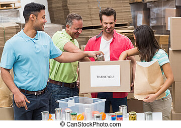Warehouse workers packing up donation boxes in a large...