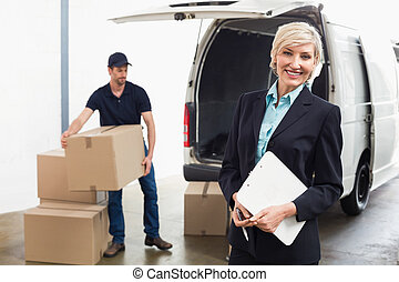 Delivery driver packing his van with manager smiling at...