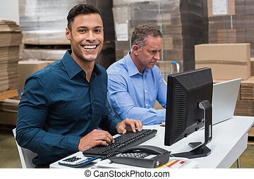 Two managers working on laptop at desk