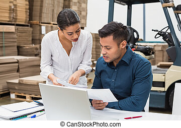 Warehouse managers working with laptop at desk