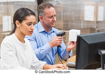 Manager scanning box while his colleague typing on laptop in...