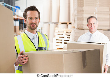 Delivery driver loading his van with boxes outside the...