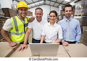 Warehouse managers and worker smiling at camera in a large...