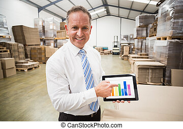 Smiling boss showing column graphic on the tablet in a large...