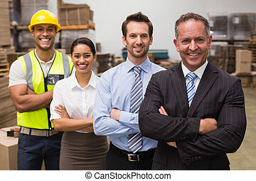 Warehouse team smiling at camera in warehouse