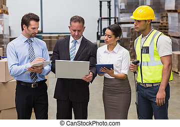 Focused warehouse team working together in a large warehouse