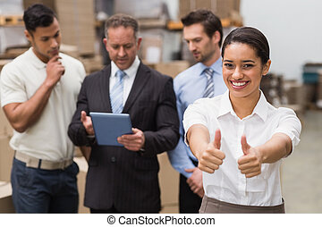 Manager showing thumbs up in front of her colleagues in a...