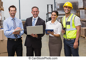 Smiling warehouse team working together in a large warehouse