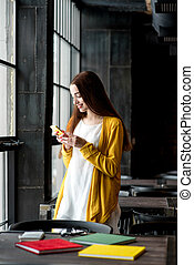 Woman using phone - Young smiling woman dressed in yellow...