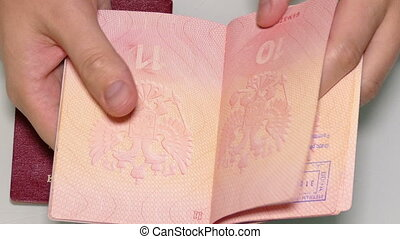 man's hands turning the pages of the passports with visas...
