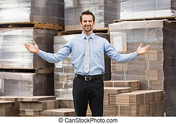 Smiling warehouse manager with hands out in a large...