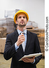 Warehouse manager wearing hard hat checking inventory