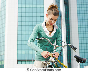 female commuter locking padlock to her bike Copy space