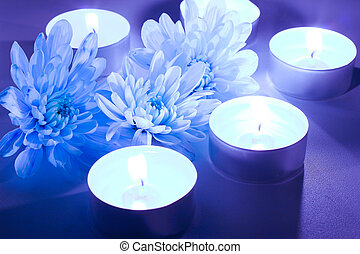 Blue flower and tea candles, spa background