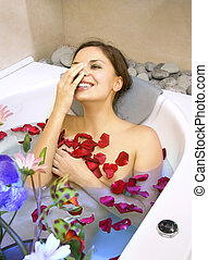 happy woman in a bath with rose-petals