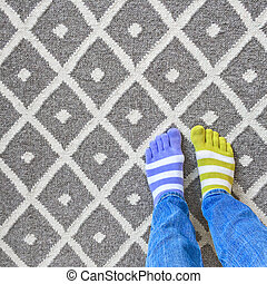 Legs in mismatched socks on gray carpet - Funny legs in...