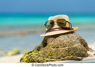 Straw hat, towel beach sun glasses and flip flops on a tropical