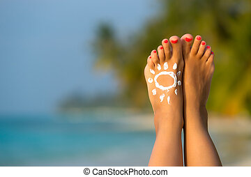 Woman foot with sun-shaped sun cream in the tropical beach...